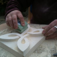 A student finishes their stone carving