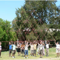 Children carry their completed tetrahedral structure across the school grounds.