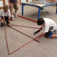 Children reason and work together to build geometric dome structure.